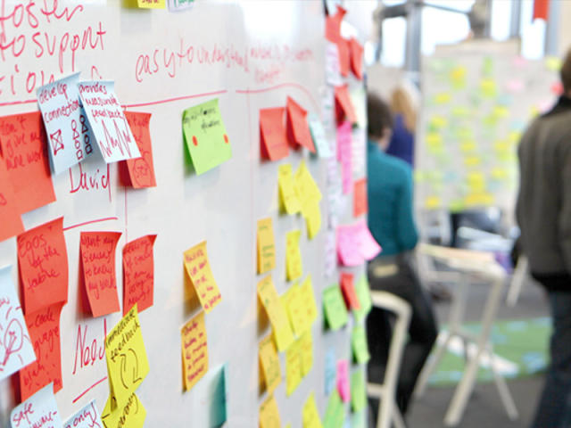 A series of whiteboards covered in post-it notes