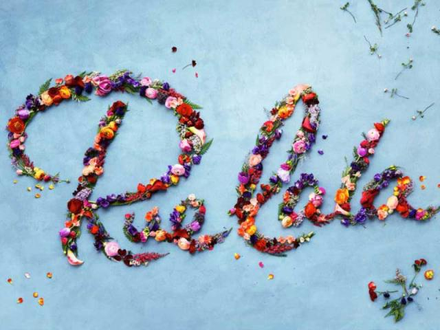 """RueLaLa"" spelled out in flower petals on a sky-blue backdrop"