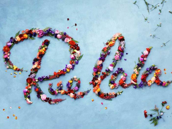 """RueLaLa"" spelled out in flower petals on a sky-blue backdrop"