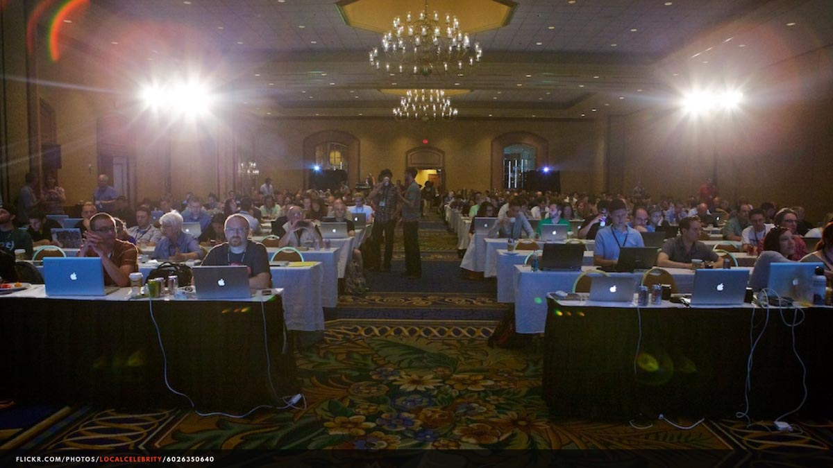 Photograph of a tech conference audience, taken from the speakers' vantage point.