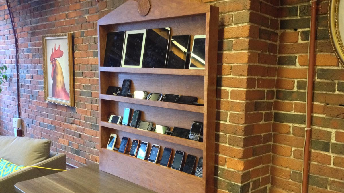 A photograph of the Bocoup Open Device Lab: a hand-made hardwood display case, with four shelves full of mobile devices and tablets.